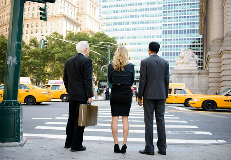 new age: Rear view of three businesspeople at crossing on a New York City street