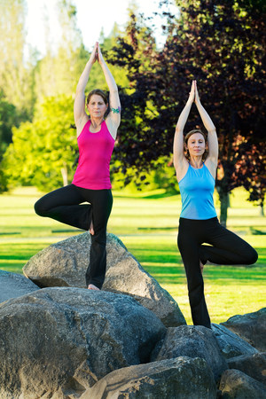 two persons only: Two women practising yoga on rocks