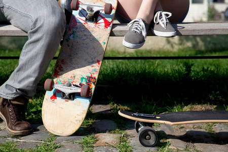 Young couple on bench with skateboards,low section LANG_EVOIMAGES
