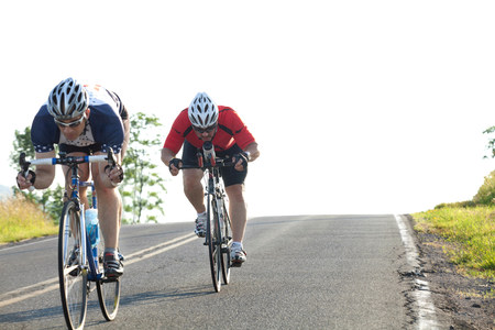Two cyclists or road,racing downhill LANG_EVOIMAGES