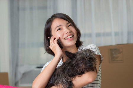 Young woman on cellphone with pet dog