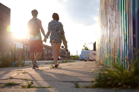 Young couple walking holding hands,rear view