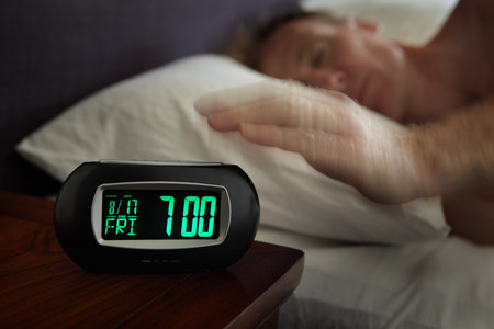 exasperation: Man reaching for alarm clock