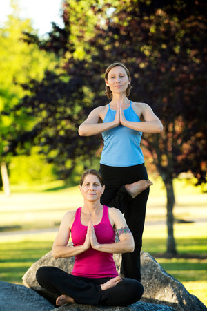 Two women in yoga poses on rocks LANG_EVOIMAGES