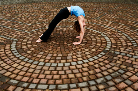 Woman bending backwards in paving stone circles LANG_EVOIMAGES