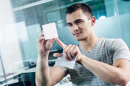 Man sticking adhesive note to window