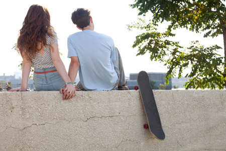 cropped out: Young couple sitting on wall holding hands