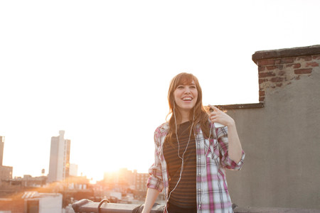 liberating: Young woman listening to music on city rooftop
