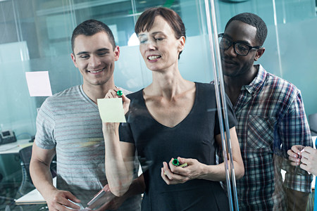 age 20 25 years: Colleagues writing on adhesive notes and sticking them to window