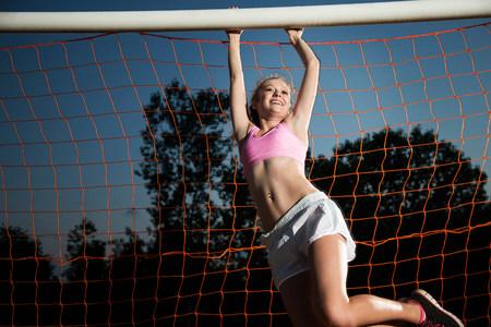 Girl hanging from soccer goal