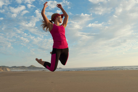 impulsive: Young woman jumping in the air on beach