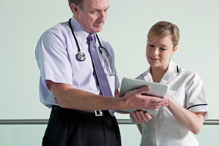 electronic organiser: Doctor and nurse discussing medical records on digital tablet LANG_EVOIMAGES