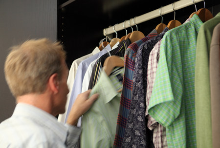 coathangers: Man taking shirt from wardrobe