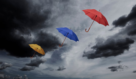 Three umbrellas floating through cloudy sky