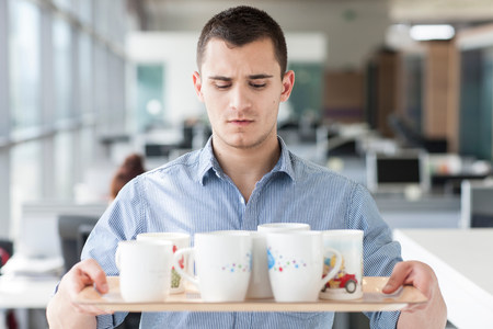 drinks after work: Nervous looking man carrying tray of mugs LANG_EVOIMAGES