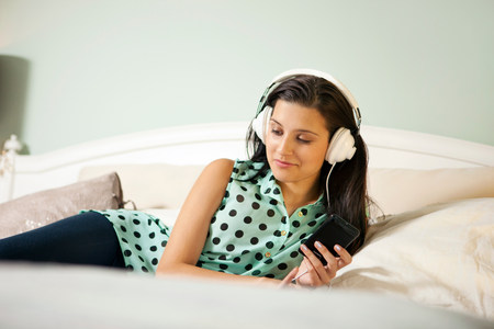 19 years old: Young woman on bed wearing earphones