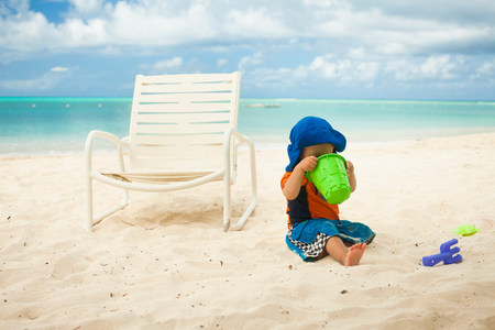 only 3 people: Little boy at the beach,looking into a bucket