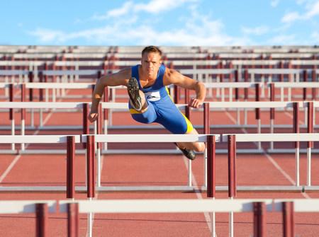 Male hurdler clearing hurdles LANG_EVOIMAGES
