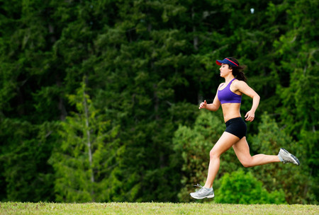 exerting: Young woman running in park