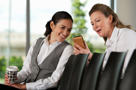 Businesswoman showing colleague smartphone LANG_EVOIMAGES