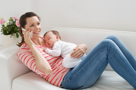 6 12 months: Mother on sofa with baby whilst on cellphone LANG_EVOIMAGES