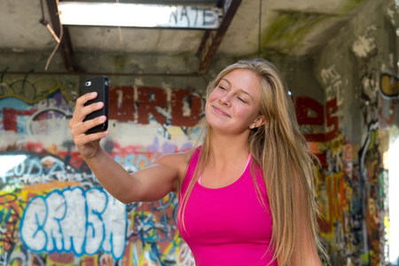 narcissist: Teenage girl taking a picture of herself on smartphone LANG_EVOIMAGES