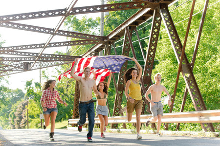 Group of friends running on bridge holding american flag LANG_EVOIMAGES