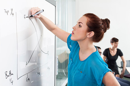 Woman drawing graph on whiteboard LANG_EVOIMAGES