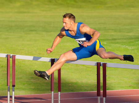 Male hurdler clearing hurdle LANG_EVOIMAGES