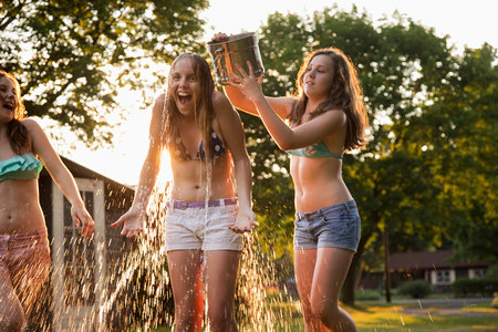 Girl pouring bucket of water over friends head