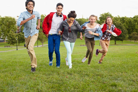 indian subcontinent ethnicity: Teenagers running in a park
