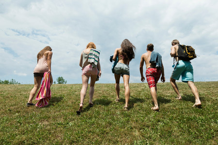 16 to 17 years old: Five friends walking in field,rear view LANG_EVOIMAGES