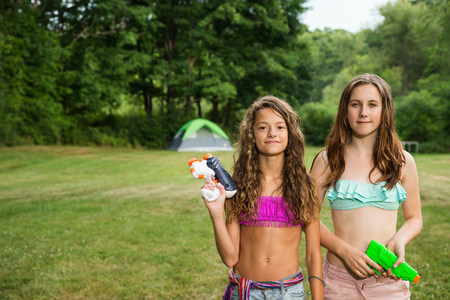 teenaged girls: Portrait of two girls holding water pistols