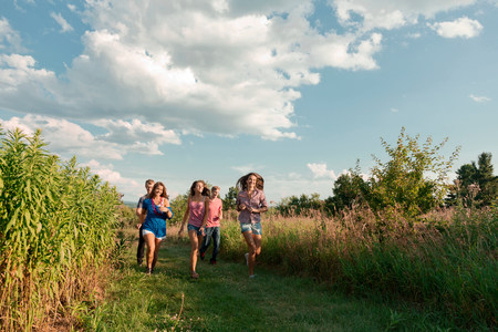 Five friends running through field