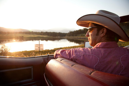 Man in cowboy hat,looking at lake from his car LANG_EVOIMAGES