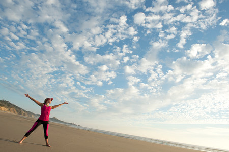 seaboard: Young woman on beach with outstretched arms LANG_EVOIMAGES