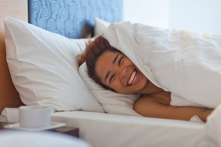 snug: Happy young woman in bed LANG_EVOIMAGES