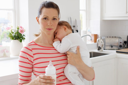 casual clothing 12 year old: Mother holding baby girl and bottle