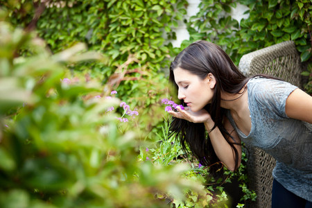 Young woman smelling flower in garden