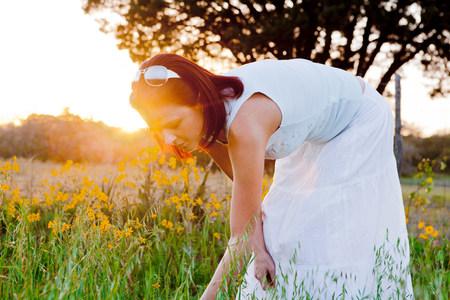 Woman picking flowers in field in sunlight