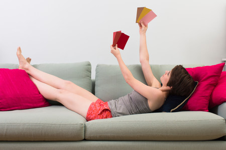 decide deciding: Young woman lying on sofa,looking at color swatches