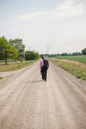travelling salesman: Businessman walking away down a dirt road LANG_EVOIMAGES