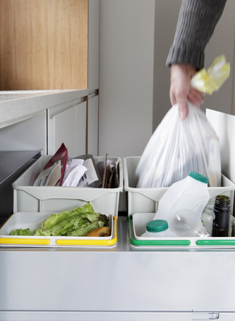 housing lot: Person removing rubbish bag from waste and recycling drawer LANG_EVOIMAGES