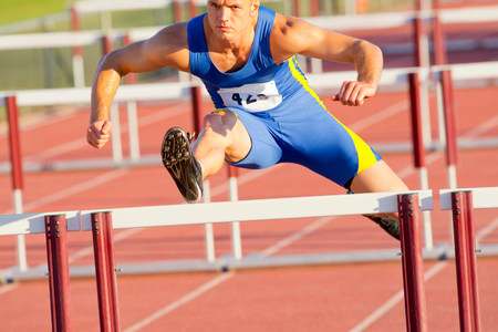 Male hurdler jumping over hurdle