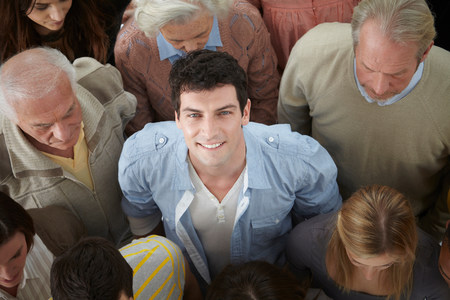 close range: Portrait of man looking up at camera in group of people,high angle