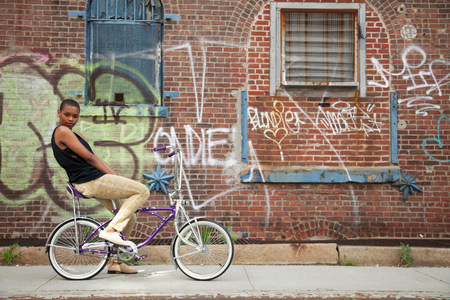 chic woman: Portrait of a young woman on bicycle by wall covered in graffiti