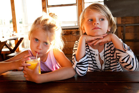 Girl drinking juice and boy looking thoughtful