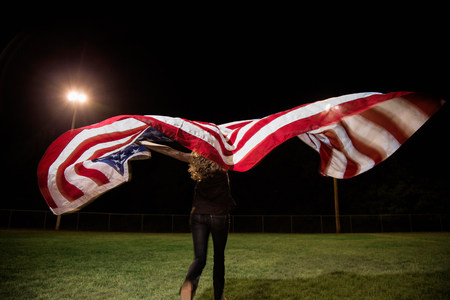 proudly: Girl holding american flag at night