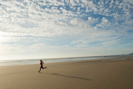 seaboard: Young woman running on beach