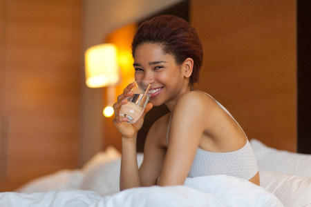 Young woman drinking a glass of water in bed